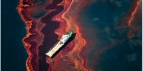Detail of Daniel Beltra's aerial photo of a ship in the middle of an oil spill caused by the Deepwater Horizon Gulf oil rig which exploded and leaked. The white ship is at a diagonal to a series of detailed ripples colored in various shades of rust red.
